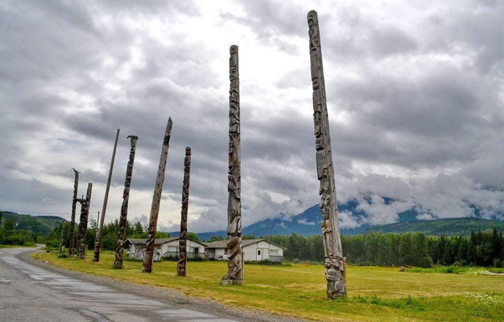 Na jednej strane cesty v osade kostol, na druhej totemy